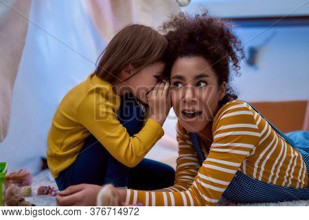 African American Woman Baby Sitter Entertaining Caucasian Cute Little Girl. They Are Gossiping And T