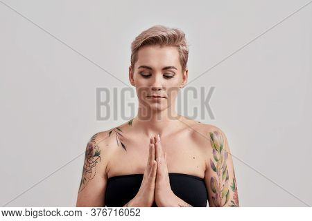 Portrait Of Half Naked Tattooed Woman Keeping Hands Folded In Praying Position And Asking For Help O