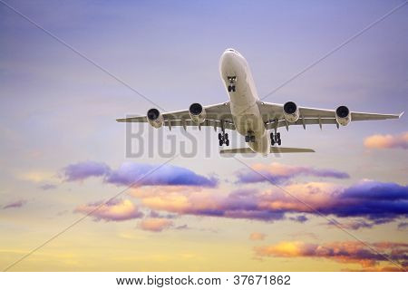 Airbus A340 jet aeroplane landing from beautiful romantic sunset sky gorgeous shades of lilac and gold. poster