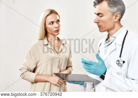Explaining Diagnosis. Professional Male Doctor In Medical Uniform Using Digital Tablet And Talking W