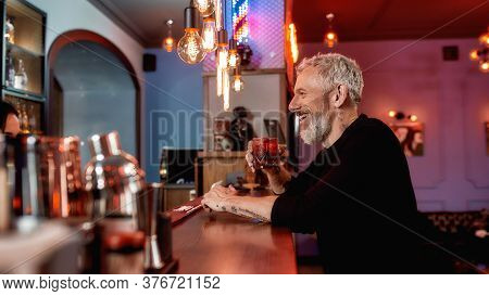 Great Day At Barbershop. Happy Middle-aged Bearded Man Drinking A Cocktail At Bar Counter While Visi