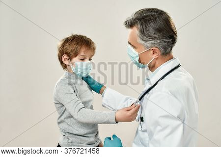 Professional Mature Doctor And Little Patient In Protective Masks. Male Pediatrician Working With Li