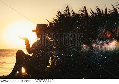 forces a girl who meditates at sunset on the sea. double exposure. Elements of this image furnished by NASA