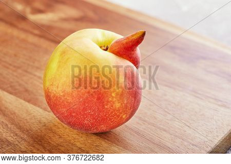 Ugly Fruit Or Vegetable. Heavily Ugly Peach Mutant On A Wooden Background. Ugly Fruits Are Not In Hi