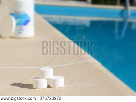 White Mini Chlorine Tablet In The Hand Of A Service Worker For Disinfection Of Swimming Pools. The B