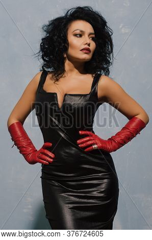 Luxurious Asian Woman Posing In Black Leather Dress And Red Gloves. Dominant Fetish Lady. - Image