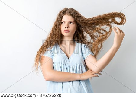 Portrait Of Attractive European Girl, Discontentedly Tilting Head And Shaking Curly Hair. Isolated O