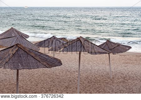 Tranquil Seascape With Rattan Umbrellas On Beach Sand With Nobody. Solitude Beach Landscape With Str