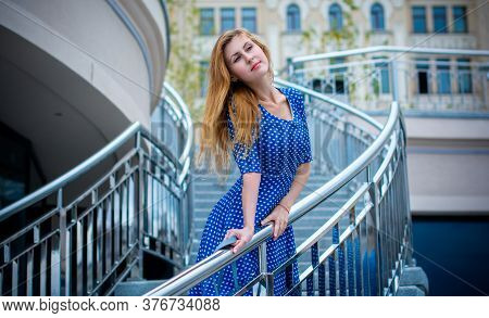 A Blonde Cute And Nice Girl In A Blue Retro Dress In A Pattern Walks Around The City On A Day Off An