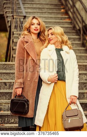 Just Relax. Girls Warm Coat On Stairs. Faux Fur Coat Fashion. Stylish Business Ladies Leather Bag. G