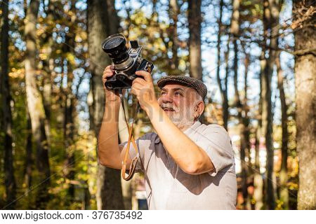 Best Camera For Professional. Old Photographer On Autumn Day. Pensioner Hold Vintage Camera In Fores