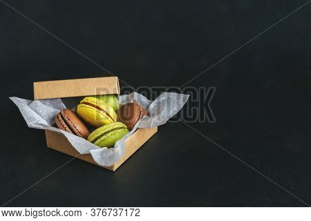 Tasty French Macarons In A Box On A Dark Background.  Yellow, Green And Brown Macarons. Place For Te