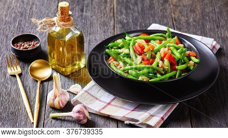 Close-up Of Stir-fry Green Beans With Onions And Tomatoes, Fry Bodi In A Black Bowl On A Wooden Tabl