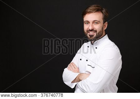 Handsome Young Bearded Male Chef Cook Or Baker Man In White Uniform Shirt Posing Isolated On Black W