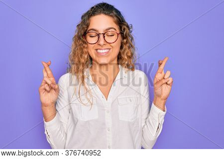 Young beautiful woman with blue eyes wearing casual shirt and glasses over purple background gesturing finger crossed smiling with hope and eyes closed. Luck and superstitious concept.