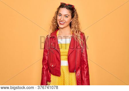 Young beautiful blonde woman pin-up with blue eyes wearing red sunglasses and jacket with a happy and cool smile on face. Lucky person.