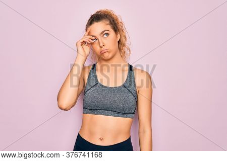 Young beautiful blonde sportswoman with blue eyes doing exercise wearing sportswear worried and stressed about a problem with hand on forehead, nervous and anxious for crisis