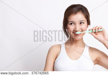 Young Asian woman in white tank top brushing teeth against white background