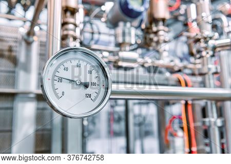 Measuring Dial Gauge. The Measuring Device Against The Backdrop Of A Complex System Of Industrial St