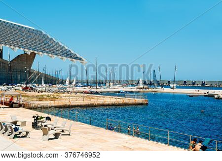 BARCELONA, SPAIN - JUNE, 24 2020: People swimming in the ocean at the Parc del Forum public park in Barcelona, Spain, highlighting the giant sculptural photovoltaic panel on the left