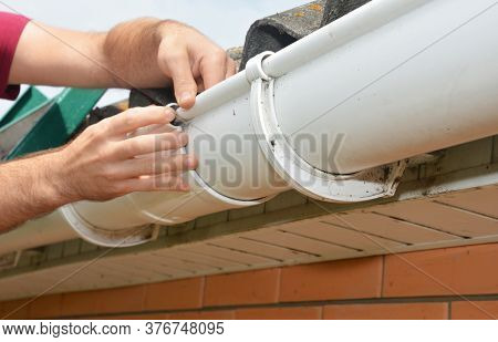 A Man Is Installing, Repairing A Roof Gutter, Fitting Union Bracket And Screwing It To The Fascia.