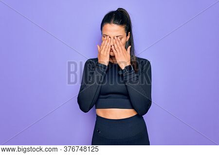 Young beautiful brunette sporty woman wearing casual sportswear over purple background rubbing eyes for fatigue and headache, sleepy and tired expression. Vision problem