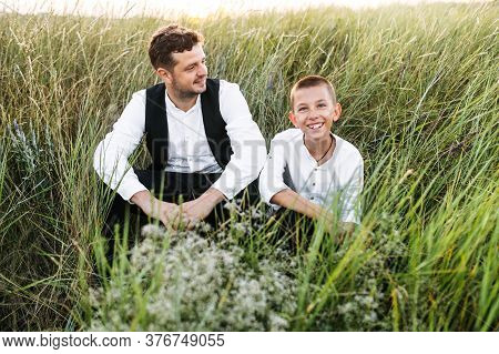 Friendship Between Father And Preteen Son. Young Dad And His School-age Son Sits On The Ground In Th