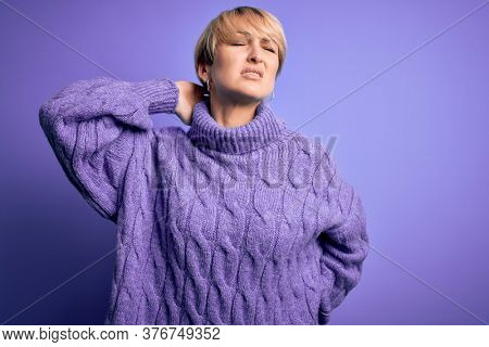 Young blonde woman with short hair wearing winter turtleneck sweater over purple background Suffering of neck ache injury, touching neck with hand, muscular pain