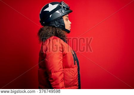 Young african american motorcyclist girl wearing moto helmet and glasses over red background looking to side, relax profile pose with natural face with confident smile.