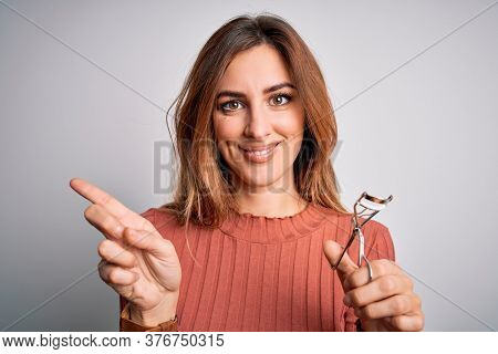 Young beautiful brunette woman using eyelash curler over isolated white background very happy pointing with hand and finger to the side