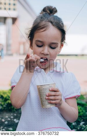 Cute Toddler Girl Eating Ice Cream With Spoon Sitting Outdoor. Real Life Happy Moments.