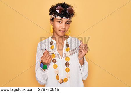 Young beautiful african american afro hippie woman wearing sunglasses and accessories doing money gesture with hands, asking for salary payment, millionaire business