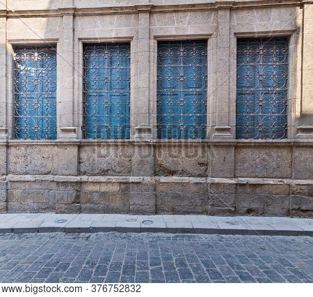 Row Of Four Windows With Ferforge Wrought Iron Grill And Closed Blue Wooden Shutters On Old Stone Br