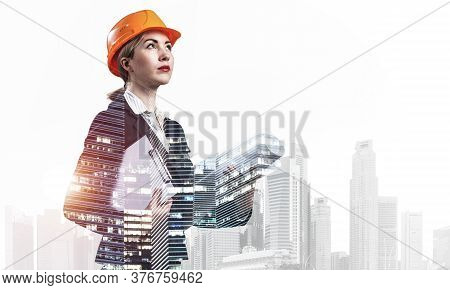 Beautiful Woman Architect Standing With Technical Drawings Looking Up. Young Specialist In Safety He