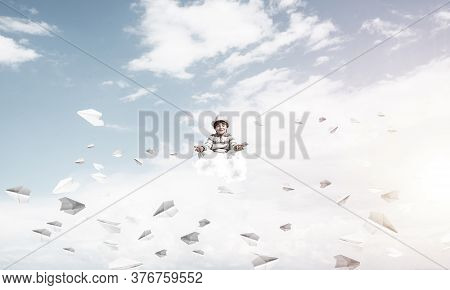 Young Little Boy Keeping Eyes Closed And Looking Concentrated While Meditating Among Flying Paper Pl