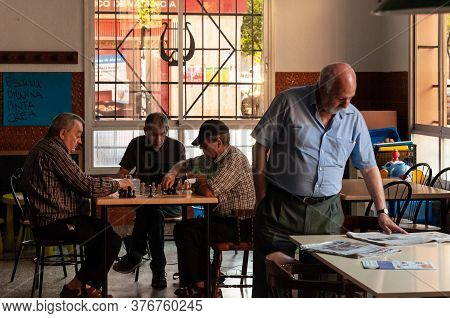 Valencia, Spain; June 2013: Four Elderly Retired People Inside A Bar In The City Of Valencia. Three