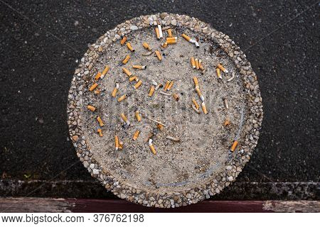 Top Of A Cigarette Ashtray Outdoor, Smoke Area, Top View, Big Round Ashtray With Sand In Public Plac