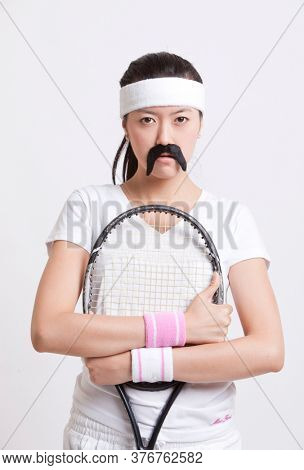 Portrait of female tennis player wearing a fake mustache against white background