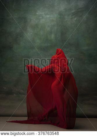 Wings Flying. Graceful Classic Ballerina Dancing On Dark Studio Background. Deep Red Cloth. The Grac