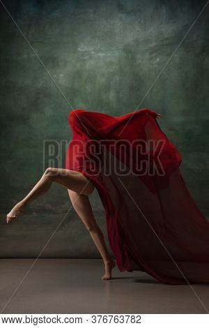 Character. Graceful Classic Ballerina Dancing On Dark Studio Background. Deep Red Cloth. The Grace,