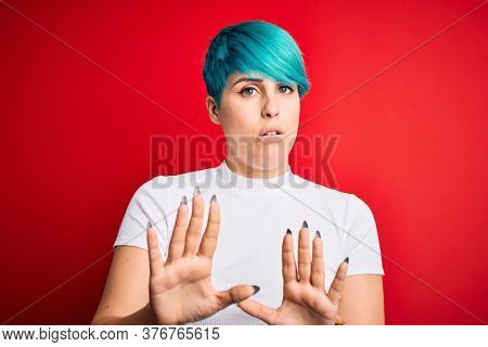 Young beautiful woman with blue fashion hair wearing casual t-shirt over red background Moving away hands palms showing refusal and denial with afraid and disgusting expression. Stop and forbidden.
