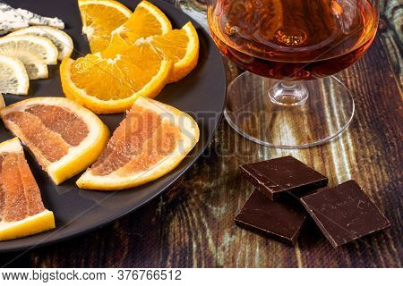 Cognac In A Glass And An Appetizer For Cognac Chocolate, Lemon, Orange And Grapefruit. Appetizer For