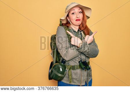 Young redhead backpacker woman hiking wearing backpack and hat over yellow background Pointing to both sides with fingers, different direction disagree
