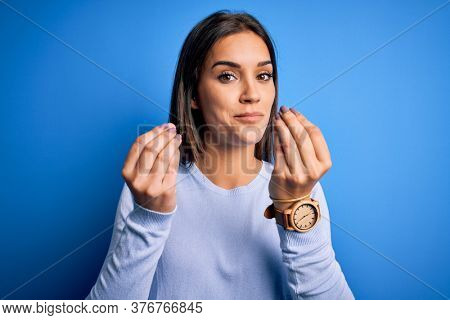 Young beautiful brunette woman wearing casual sweater standing over blue background doing money gesture with hands, asking for salary payment, millionaire business