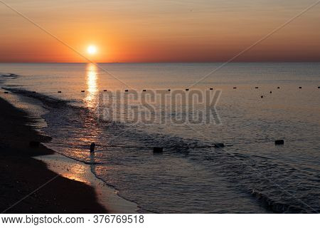 Awesome Dawn Over Calm Sea On Beach Landscape With Nobody. Sunrise Seascape With Surf Waves And Buoy