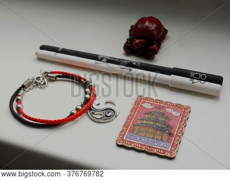 A Composition Of A Chinese Red Tortoise Figurine, A Black And White Pen, A Bracelet With A Yin Yang