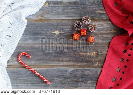 New Year Flat Lay: Christmas Caramel Candy Cane, Red Tiny Gifts, Cones, White Woolen Plaid And Red T
