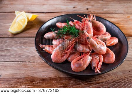Appetizing Boiled Shrimp On A Skewer In A Black Plate On A Wooden Surface Among Lemon. The Concept O