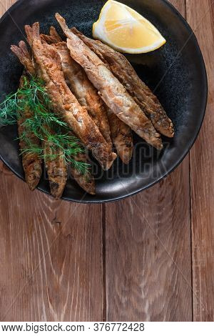 Appetizing Fried Capelin On A Black Plate Stands On A Wooden Surface. Simple Rustic Food Concept