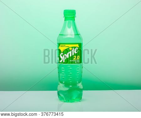 0.5-liter Plastic Bottle Of Sprite Drink On A Green Background With Lemons And Limes. Sprite Is A Le